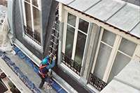Homme qui monte sur une �chelle de toit