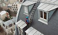 Homme qui travaille sur une �chelle de toit